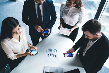 Group of office workers using devices in conference room