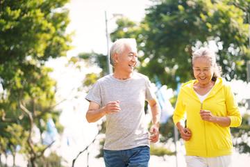 senior asian couple running in park