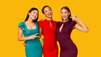Three Diverse Girlfriends Gesturing Victory Sign Posing On Yellow Background