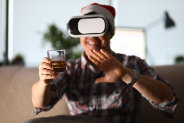 Tuinposter Bar Man sit at sofa hold glass in hand and using vr gogles
