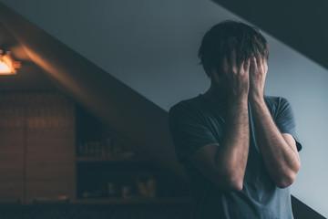 Fototapeta Depressed man is crying by the window of kitchen loft obraz