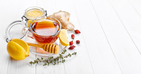 Ginger tea with lemon honey Rose Hip and thyme at white wooden board in rustic style.