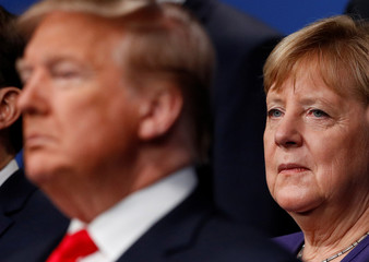 U.S. President Donald Trump and Germany's Chancellor Angela Merkel pose for the family photo during the annual NATO heads of government summit at the Grove Hotel in Watford