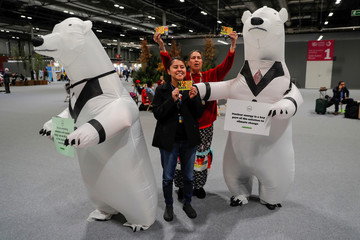 Anti-nuclear activists stand next to men dressed as polar bears holding banners advocating for nuclear energy as a solution for climate change during the U.N. climate change conference (COP25) in Madrid