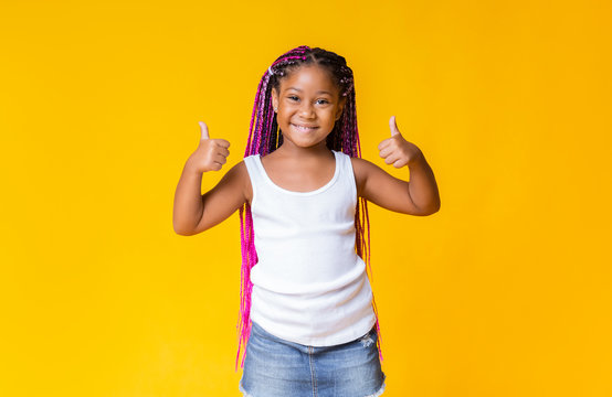 Pretty little african american girl gesturing thumbs up and smiling