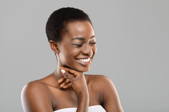 Beauty portrait of joyful black woman sincerely laughing over gray background