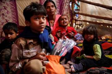 "A volunteer sits with the children displaced with their family member during the ""Gadhimai Mela"" festival held at Bariyarpur"