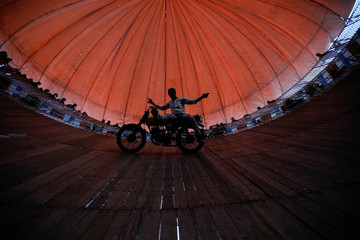 "A stuntman performs on the well of death during the ""Gadhimai Mela"" festival at Bariyarpur"