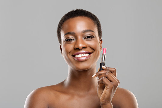 Portrait of pretty afro girl with pink lipstick in hand