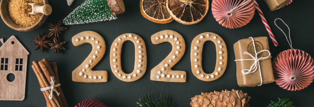Ginger biscuits of the form of numbers banner 2020 new year ginger cookies and Christmas decor on dark background.