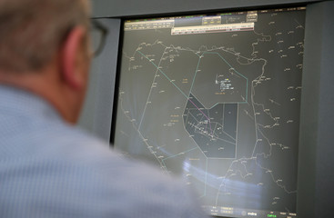 An air traffic controller looks at a map of flights above the country in the control tower at Sarajevo airport in Sarajevo