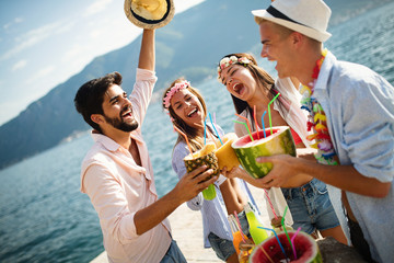 Group of friends having fun at summer party and drinking cocktail