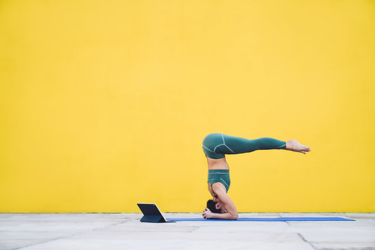 Sporty woman stretching on yoga mat on yellow background