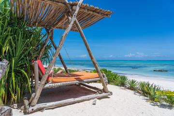 Wooden swing under a canopy on the tropical beach near sea, island Zanzibar, Tanzania, East Africa
