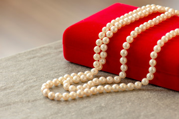 Beautiful natural pearl necklace laid on red velvet jewelry box.