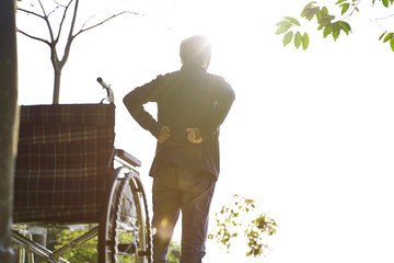 asian old man standing by wheelchair