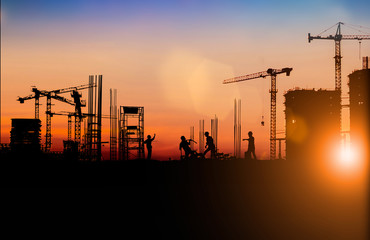 Silhouette of Survey Engineer and construction team working at site over blurred  industry background with Light fair Film Grain effect.Create from multiple reference images together