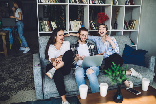Group of young hipsters laughing and sitting on couch