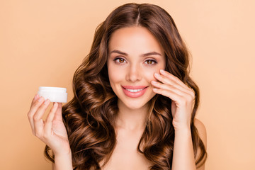 Close up photo of positive charming curly haired girl apply cream jar to make skin smooth perfect...