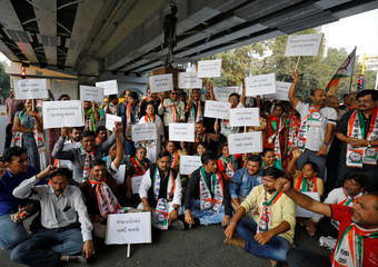 Supporters of India's main opposition Congress party hold placards as they shout slogans during a protest against the alleged rape and murder of a 27-year-old woman, in Ahmedabad