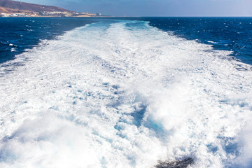 Water trail foaming behind a ferry boat in Atlantic ocean between Canary islands, Spain. Fuerteventura island on the background