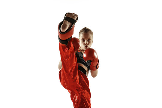 Young female kickboxing fighter training isolated on white background. Caucasian blonde girl in red sportswear practicing in martial arts. Concept of sport, healthy lifestyle, motion, action, youth.