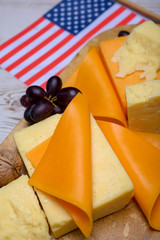 Cheese collection, blocks and slices of yellow and matured american cheddar cheese with flag of USA