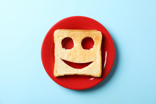 Plate and bread toast with happy face on blue background, top view