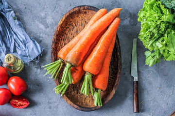 Photo of Fresh Carrots On A Plate. On wooden dark background. Bunch of fresh carrots with green leaves.Top view. Slice of carrots. Carrot around vegetables, salt, black pepper, corn, broccoli. Image