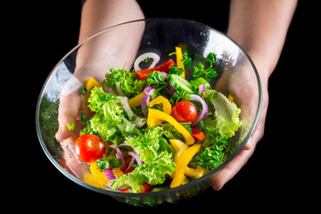 cut vegetables in glass dish in woman hands