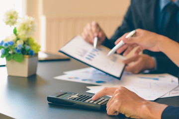 Businessman analysis on Graph data paper  using calculator, finance concept in office.