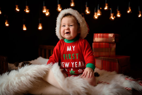 7 month old girl in a red Christmas costume on a background of retro garlands sits on a fur