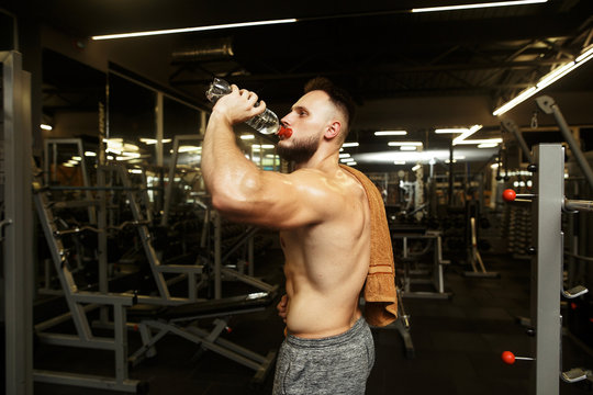 Sports handsome trainer drinking water after the raining in the empty gym.