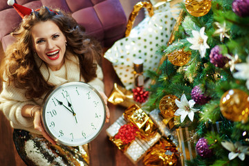 middle age woman showing clock under decorated Christmas tree