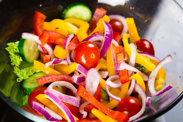 Closeup of cut vegetables preparing for salad in the glass dish