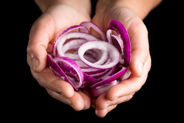 Red onion cut rings in palms