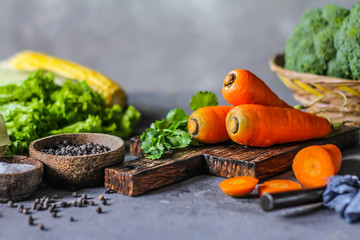 Photo of Fresh Carrots On Wooden Cutting Board. On wooden Dark Background. Slice of carrots with green leaves. Carrot around vegetables, salt, black pepper, corn, broccoli. Drops of water. Image