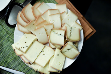 close up on slices of cheese at raclette party