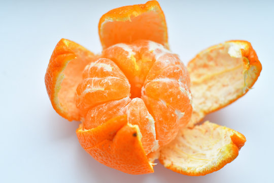peeled tangerine on a white background.Orange fruits and peeled segment Isolated. Pile of orange segments