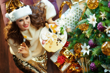 smiling elegant woman eating cheese and holding platter