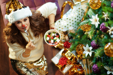 woman with healthy salad making red nose with cherry tomato