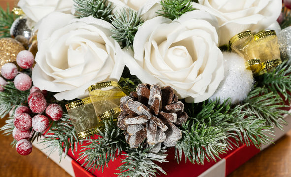 Close-up of Christmas bouquet with flowers and spruce with snow.