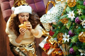 trendy woman eating hamburger near Christmas tree
