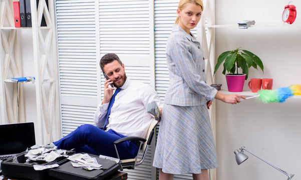 Woman cleaning up office while boss has phone conversation. Gender concept. Gender and career. Personal assistant. Equal rights for education work and salary. Gender discrimination in business life