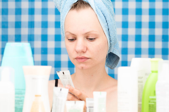 Portrait of girl without makeup in bathroom surrounded by cosmetics