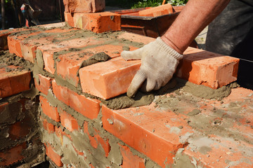 Bricklayers hands in masonry gloves bricklaying house wall. Bricklaying,  Masonry, Brickwork close up