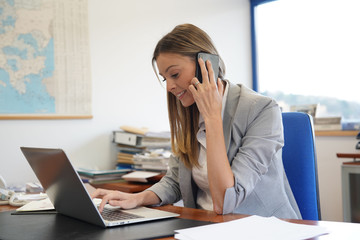 Businesswoman in office talking on phone