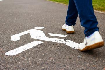 White pedestrian sign on sidewalk and feet of woman pedestrian