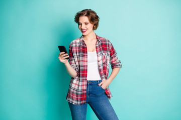 Portrait of positive cheerful modern girl use cell phone read social media information follow comment repost news wear casual style outfit isolated over turquoise color background