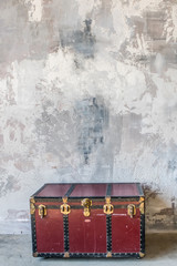 chest in front of the grunge shabby gray wall. Interior background